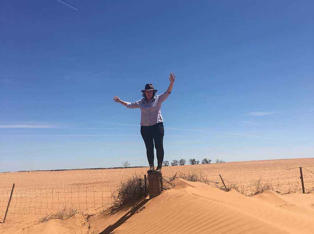 Suzie Jacobs, a member of the East Loddon Food Share Program Inc stands on a strainer post in front of a paddock that was in crop for the 2019 season at Meringur.