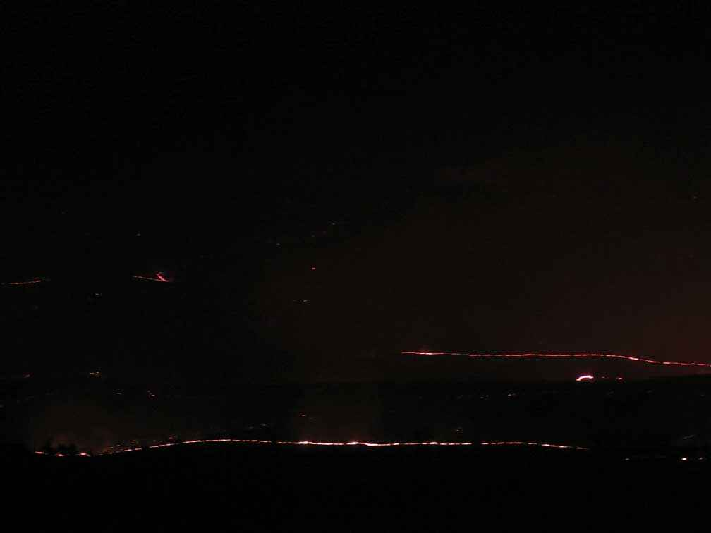 The glowing rim of the uncontrolled fire seen from a hilltop at John Robinson and Farideh Lashkary's property at Bylands on Sunday 9 February 2014.