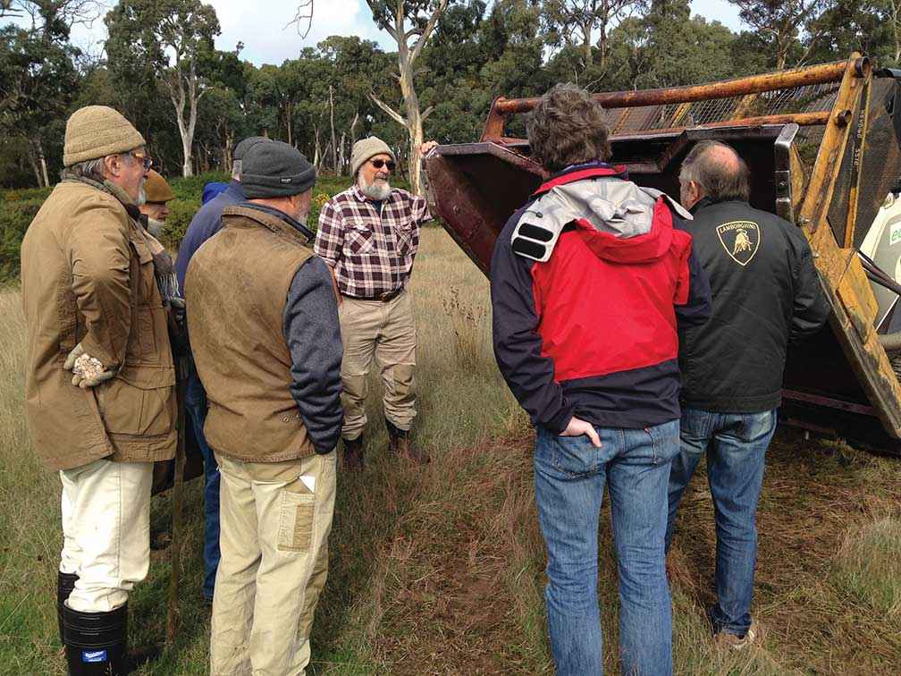 Landholders inspect a gorse mowing attachment at a Tylden Landcare Group field day.