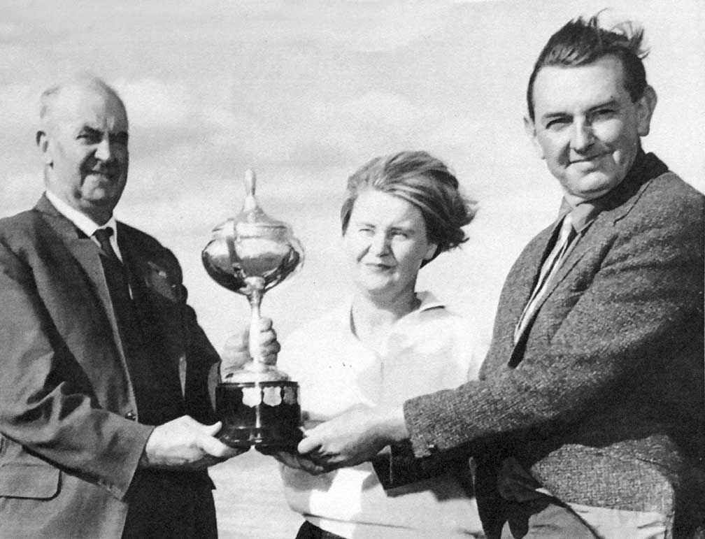 Mr A.F. Saunders (left) from the Soil Conservation Authority presents the Hanslow Cup for Soil Conservation in the Otway District to Helen and Geoff Henderson at their property Inverness at St Leonards in 1968. They are standing in front of a large, recently constructed dam on the property.